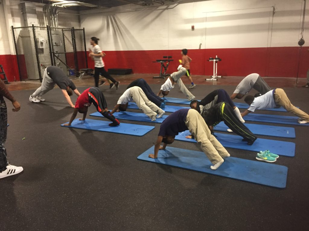 Students at the Downtown Boxing Gym participate in a Monday evening yoga class.